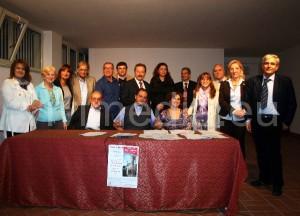 Un gruppo di giurati, vincitori e segnalati stretti intorno a don Gioacchino Lanzillo dopo la premiazione
